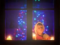 逗人喜爱的小男孩,坐窗口在晚上,看户外, 库存照片