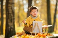 逗人喜爱的小男孩绘画在金黄秋天公园 免版税库存照片