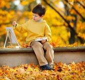 逗人喜爱的小男孩绘画在金黄秋天公园 免版税图库摄影