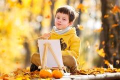 逗人喜爱的小男孩绘画在金黄秋天公园 图库摄影