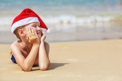 逗人喜爱的小男孩画象圣诞老人帽子的 免版税库存图片