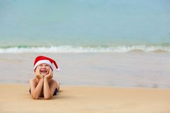 逗人喜爱的小男孩画象圣诞老人帽子的 免版税库存照片