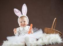 逗人喜爱的小的兔宝宝用红萝卜 库存照片