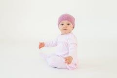 逗人喜爱的小的女婴佩带的帽子坐被隔绝的地板 库存照片