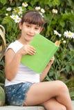 逗人喜爱的小的学校女孩阅读书 免版税库存图片