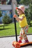 逗人喜爱的小的小孩女孩骑马滑行车在城市,孩子炫耀 垂直 免版税库存照片