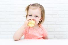 逗人喜爱的小的2年女孩用苹果在家 库存图片