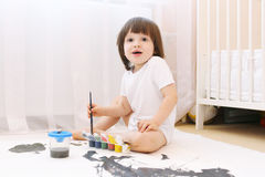 逗人喜爱的小的2年有刷子和树胶水彩画颜料油漆的男孩在家 库存照片