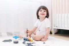 逗人喜爱的小的2年有刷子和树胶水彩画颜料的男孩 免版税库存图片