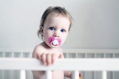 逗人喜爱的小的1年有钝汉的女孩在白色床上 库存图片