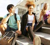 逗人喜爱的小组在大学大厦的teenages有书huggings的,回到学校 免版税库存图片