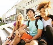 逗人喜爱的小组在大学大厦的teenages有书huggings的,回到学校 免版税图库摄影