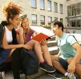 逗人喜爱的小组在大学大厦的teenages有书huggings的,回到学校 免版税库存照片
