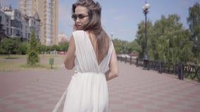 逗人喜爱的少女佩带的太阳镜和走一件长的白色夏天时尚的礼服户外 一名俏丽的妇女的休闲 股票录像