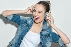逗人喜爱的少妇使用耳机 库存图片