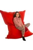 逗人喜爱的少妇坐居住的ro的红色装豆子小布袋沙发椅子 库存图片