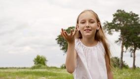 逗人喜爱的少年女孩吹的雏菊瓣从棕榈手到照相机 无忧无虑的从手的少女吹的花瓣 股票录像