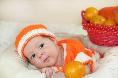 逗人喜爱的少量有滑稽的好奇面孔的天新出生的婴孩在a穿戴了 免版税库存图片