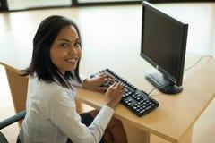 逗人喜爱的工作亚洲妇女计算机 免版税图库摄影