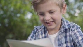 逗人喜爱的帅哥接近的画象看纸片的方格的衬衣的在公园 夏令时休闲 影视素材