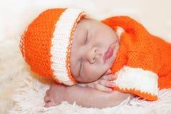 逗人喜爱的平安的睡觉的新出生的婴孩在一个被编织的桔子穿戴了 图库摄影