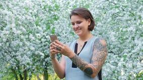 逗人喜爱的年轻棕色毛发的妇女与智能手机聊天在开花的苹果树庭院里在好日子 生活方式 影视素材