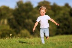 逗人喜爱的年轻男孩跑草甸 库存图片