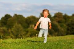 逗人喜爱的年轻男孩跑草甸 免版税库存照片