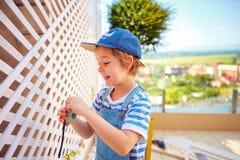 逗人喜爱的年轻男孩,孩子帮助有整修的父亲wodden在屋顶露台区域的荫径墙壁 免版税库存照片