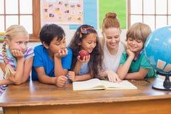 逗人喜爱的微笑对照相机的学生和老师在教室 免版税库存图片