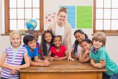逗人喜爱的微笑对照相机的学生和老师在教室 免版税图库摄影