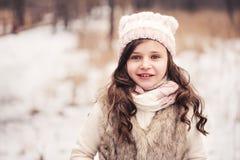 逗人喜爱的微笑的儿童女孩冬天画象在多雪的森林里 免版税库存照片