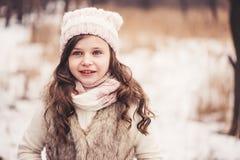逗人喜爱的微笑的儿童女孩冬天画象步行的在多雪的森林里 免版税库存照片