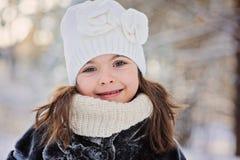 逗人喜爱的微笑的儿童女孩冬天画象步行的在晴朗的多雪的森林里 免版税库存照片