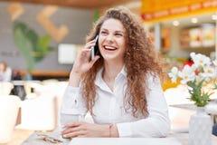 逗人喜爱的微笑的卷曲妇女享受与最好的朋友的电话交谈,份额最新的新闻,笑快乐,享用外带的咖啡  免版税库存图片