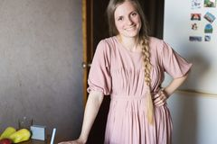 逗人喜爱的微笑的女孩在厨房里 免版税图库摄影