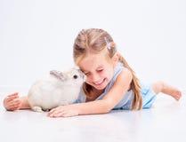 逗人喜爱的微笑的女孩用一只白色兔子 库存照片