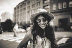 逗人喜爱的微笑的女孩画象太阳镜的有城市大厦的在背景中 库存照片