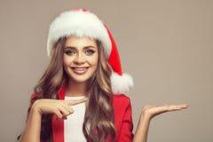 逗人喜爱的微笑的妇女画象圣诞老人帽子的 免版税库存图片