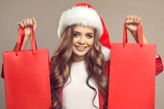 逗人喜爱的微笑的妇女画象圣诞老人帽子的 免版税库存照片