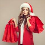 逗人喜爱的微笑的妇女画象圣诞老人帽子的 库存图片