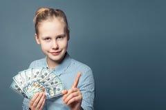 逗人喜爱的微笑的富有的少年女孩和金钱现金在蓝色背景的美元 免版税库存照片