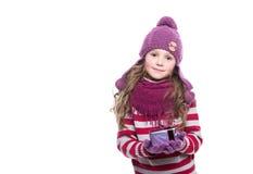 逗人喜爱的微笑的小女孩佩带的紫色在白色背景编织了围巾、帽子和手套,拿着圣诞节礼物被隔绝 库存照片