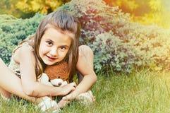 逗人喜爱的微笑的小女孩拿着玩具熊和坐g 库存照片