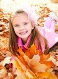 逗人喜爱的微笑的小女孩秋天画象有槭树的离开 免版税库存图片