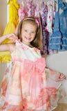逗人喜爱的微笑的小女孩从衣橱选择礼服 免版税图库摄影