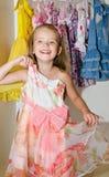 逗人喜爱的微笑的小女孩从衣橱选择礼服 库存图片
