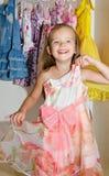 逗人喜爱的微笑的小女孩从衣橱选择礼服 免版税库存图片