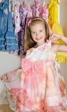 逗人喜爱的微笑的小女孩从衣橱选择礼服 图库摄影