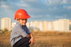 逗人喜爱的微笑的小男孩佩带的盔甲坐新的大厦背景在日落 库存照片